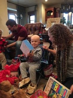 Amos opening Christmas presents and enjoying himself greatly