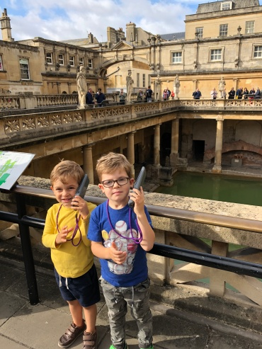 The boys listening to the audio tour at the Roman Baths.
